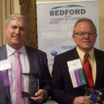 Watt Foster, CEO and President of Foster Fuels, stands next to Bill Moss both holding Bedford Area Chamber of Commerce awards.
