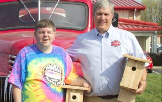 Chris Russell and Watt Foster Stand together holding handcrafted birdhouses